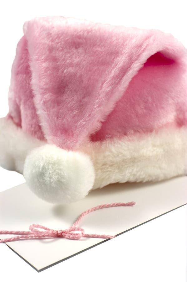 Sombrero rosado de Santa en el sobre blanco foto de archivo