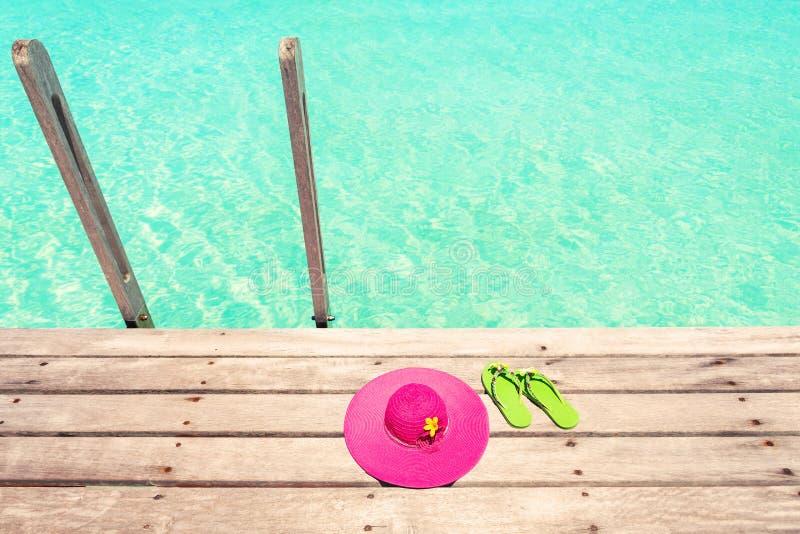 Sombrero rosado grande del sol y sandalia verde de la playa en la cubierta de madera cerca imagen de archivo