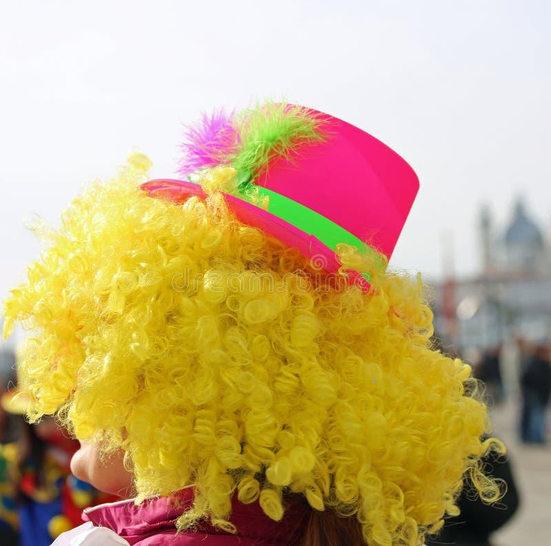 Sombrero rubio de la peluca y del fucsia de un payaso que se realiza para los niños foto de archivo libre de regalías