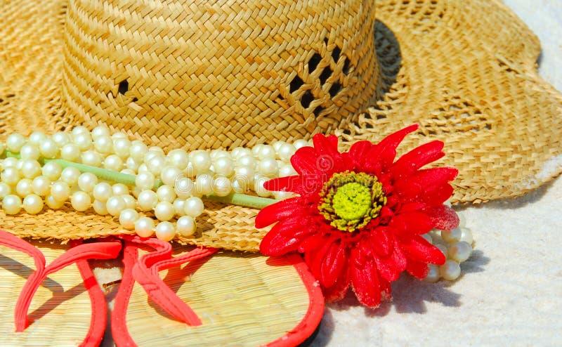 Sombrero, sandalias y perlas en la playa fotografía de archivo libre de regalías