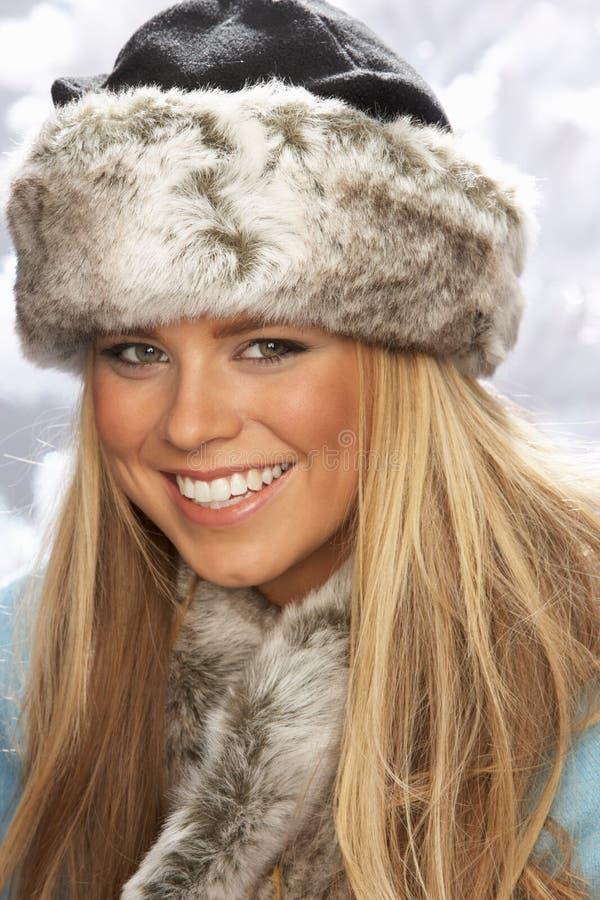 Sombrero y abrigo de piel de la mujer que desgastan joven en estudio fotografía de archivo