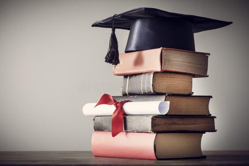 Sombrero y diploma de la graduación con el libro en la tabla imagenes de archivo