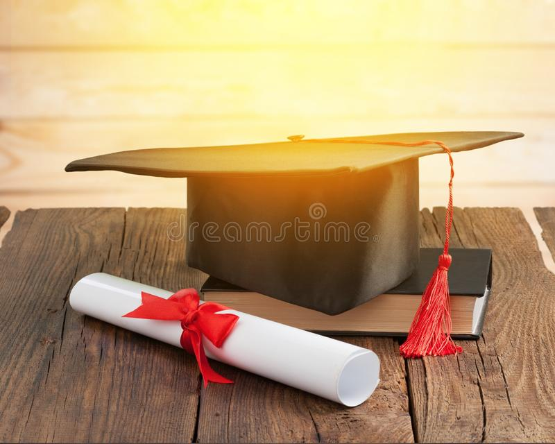 Sombrero y diploma de la graduación en fondo de madera foto de archivo libre de regalías