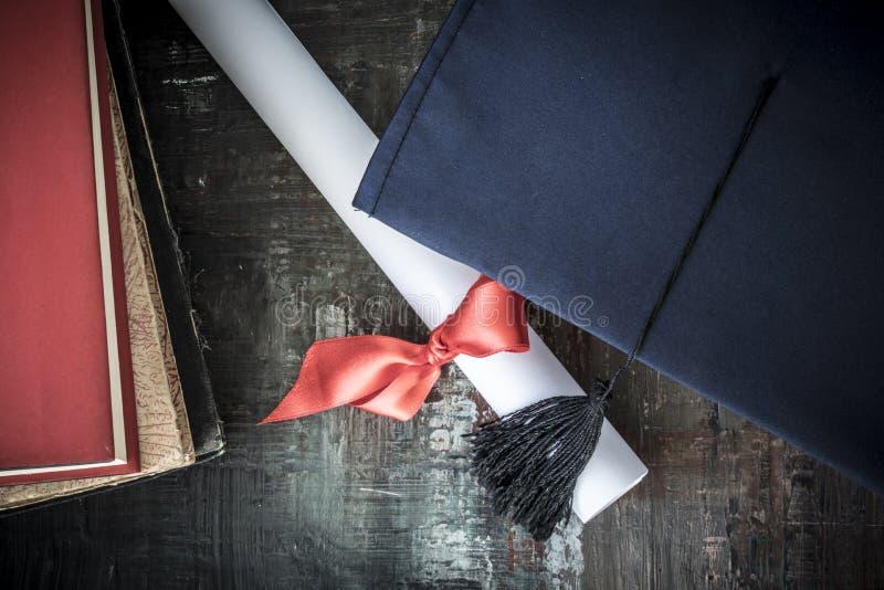 Sombrero y diploma de la graduación en la tabla fotografía de archivo libre de regalías