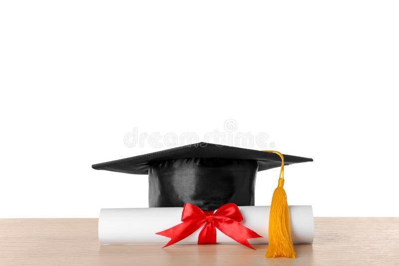 Sombrero y diploma de la graduación en la tabla fotos de archivo