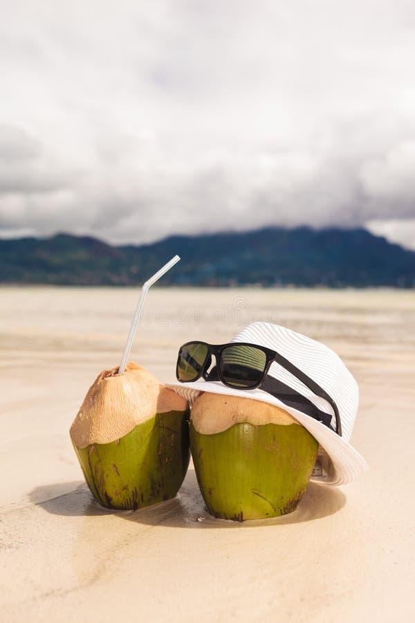 Sombrero y gafas de sol con dos cócteles de la nuez de los Cocos en la playa fotografía de archivo