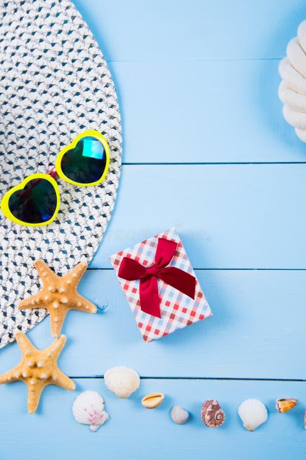 Sombrero y gafas de sol con las cáscaras, las estrellas de mar, la caja de regalo y la cuerda encendido imagenes de archivo