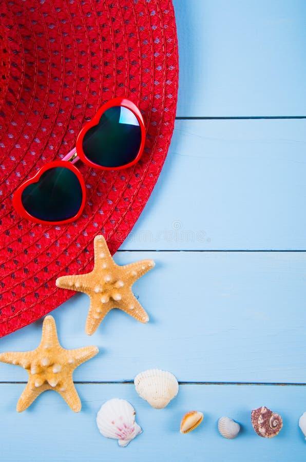 Sombrero y gafas de sol con las cáscaras y estrellas de mar rojos en de madera azul imagen de archivo