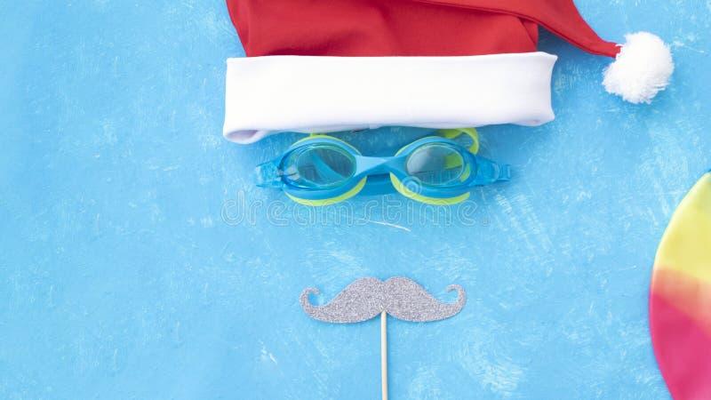 Sombrero y gafas de sol rojos de la Navidad cerca de la piscina Lugar para el texto imagen de archivo