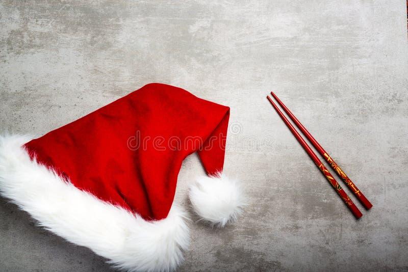 Sombrero y palillos rojos de santa en una tabla concreta gris fotografía de archivo