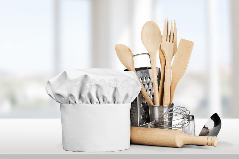 Sombrero y utensilios blancos del cocinero en la tabla fotografía de archivo libre de regalías