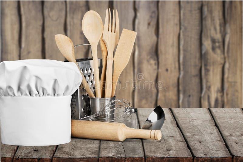 Sombrero y utensilios blancos del cocinero en la tabla imagen de archivo