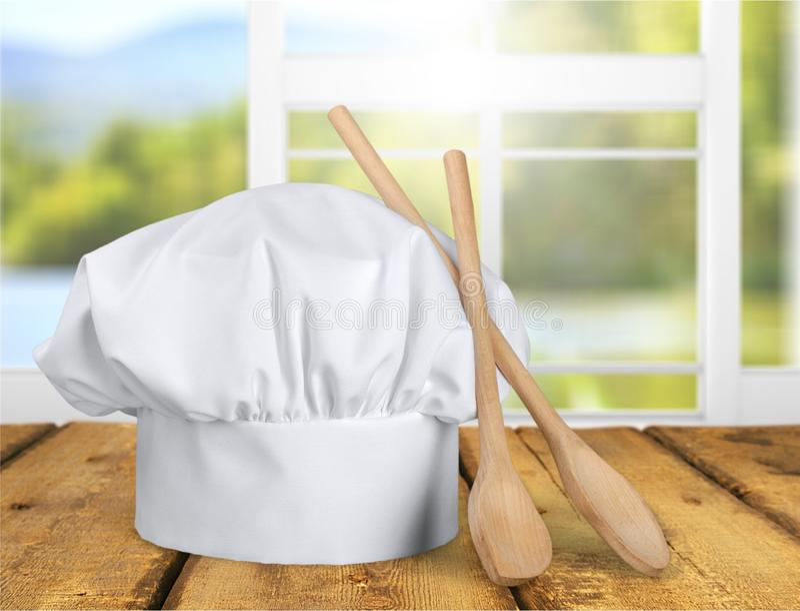 Sombrero y utensilios blancos del cocinero en la tabla fotos de archivo