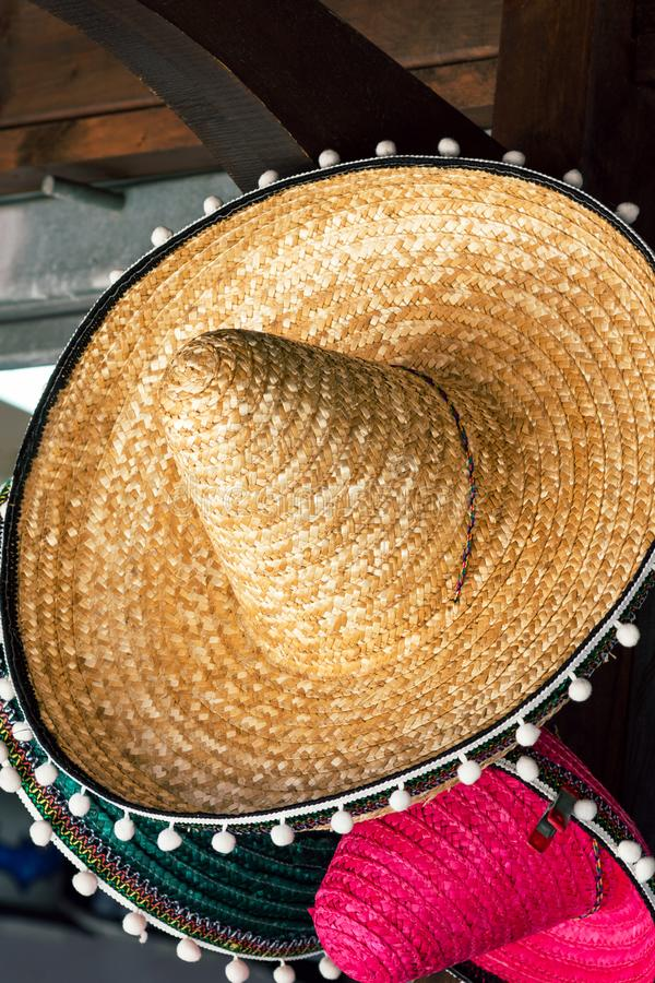 Sombreros tejidos paja mexicana Handcrafted del sombrero del artesano que cuelgan en el mercado local en tablón de madera Cinco d imagenes de archivo