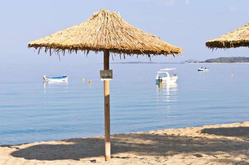 Sombrilla cubierta con paja en una playa reservada para for Sombrillas para piscinas