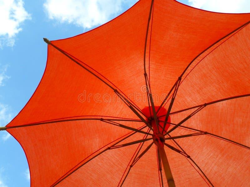 Sombrilla de color naranja vibrante contra el cielo azul vivo y la nube blanca imagenes de archivo