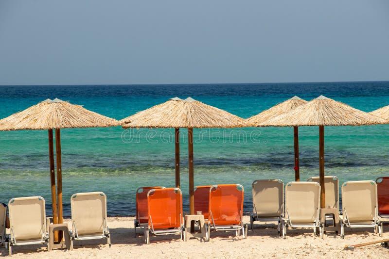Sombrillas con sillas en la playa en Milos imagen de archivo