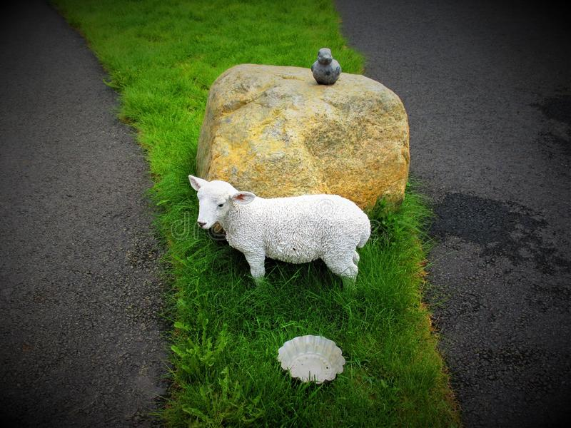 A lamb in porcelain in the garden, while a duck in stone up on a stone fits it royalty free stock photos