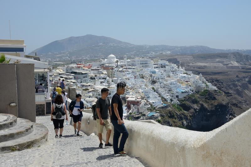 asiatic tourists looking the panoramic view from the street of Thira in Santorini island royalty free stock image