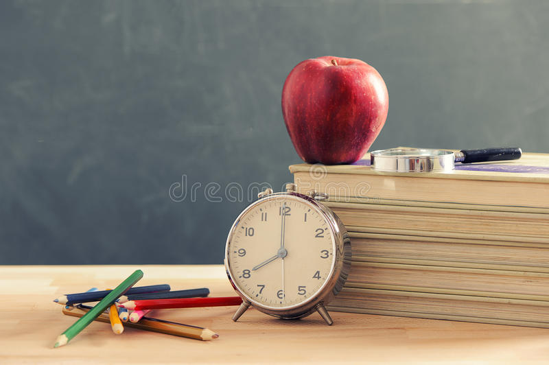Some books and a pencil holder on a wooden table. Red apple is standing on the books. stock images
