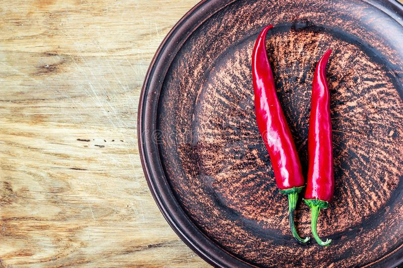 Some chili peppers on dark plate, fresh red ripe hot chilli on old wood board background with copy space, guinea pepper or bird pe royalty free stock photos
