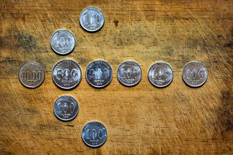Some coins on a wooden surface. Coin, currency, banking, finance, financial, cent, euro, isolated, money, pile, concept, white, gold, nickel, quarter, wealth stock photography