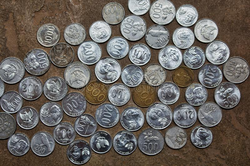 Some coins on a wooden surface. Coin, currency, banking, finance, financial, cent, euro, isolated, money, pile, concept, white, gold, nickel, quarter, wealth stock image