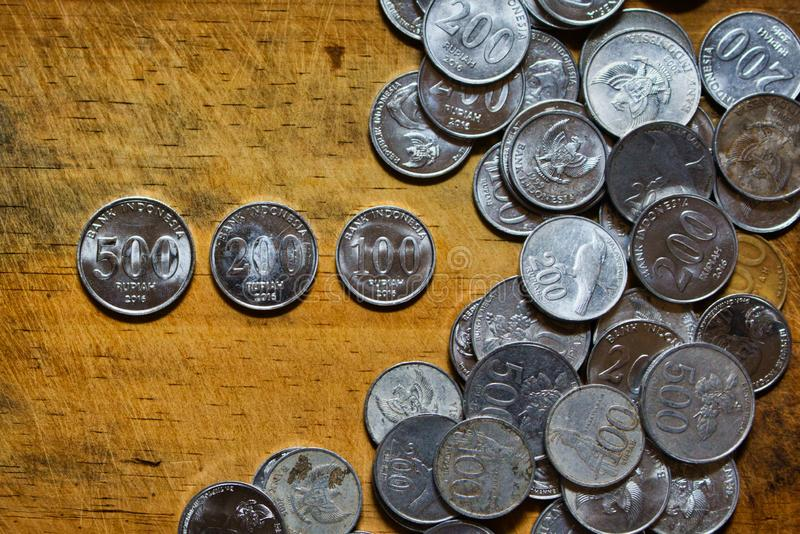 Some coins on a wooden surface. Coin, currency, banking, finance, financial, cent, euro, isolated, money, pile, concept, white, gold, nickel, quarter, wealth stock photo