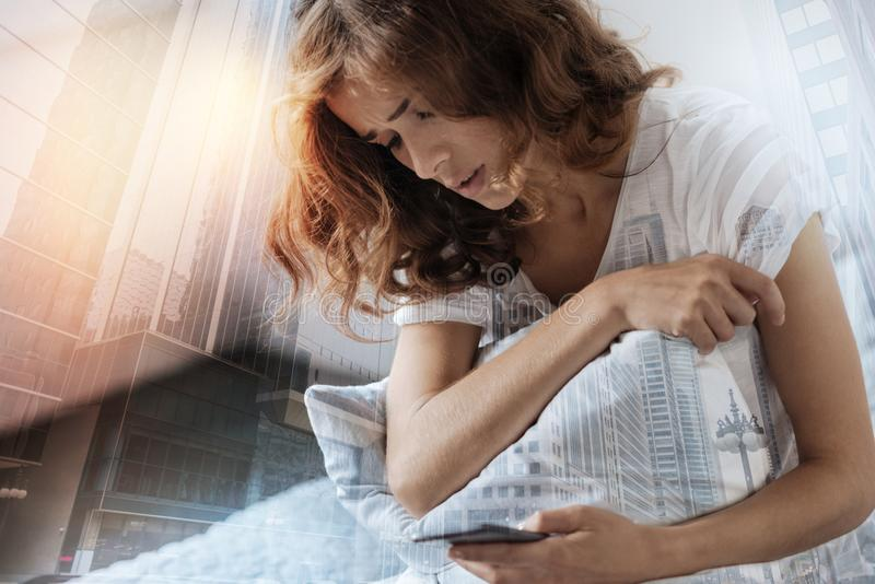 Upset female person typing message. Some difficulties. Depressed brunette bowing head and embracing pillow while looking at her telephone stock images