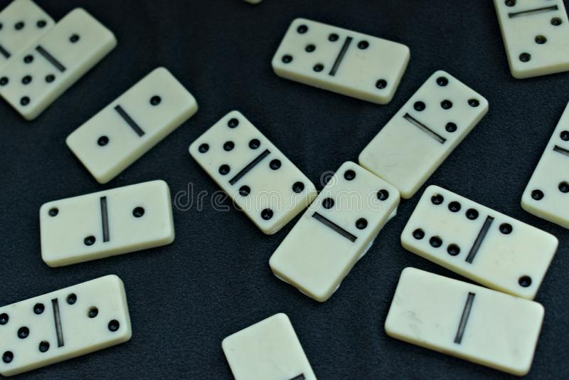 Some dominoes pieces thrown on a black background stock photography