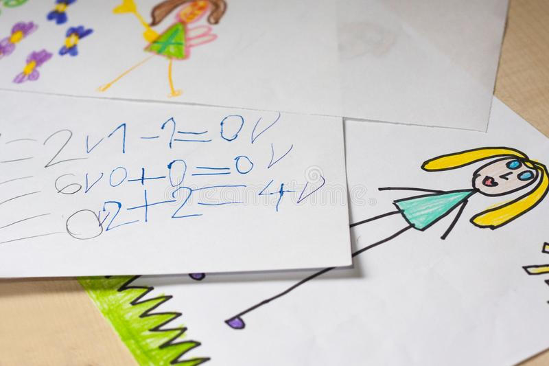 Some children`s drawings and calculations. Some elementary school child`s drawings and simple calculations on white paper stock photos