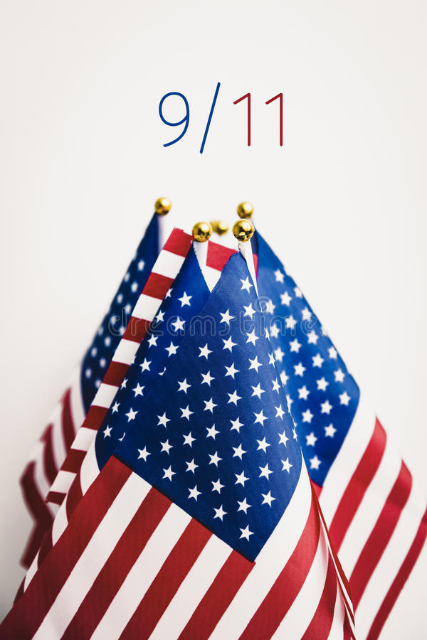 Text 9/11 for the September 11 attacks. Some flags of the United States and the text 9/11 for September the 11th against an off-white background royalty free stock images
