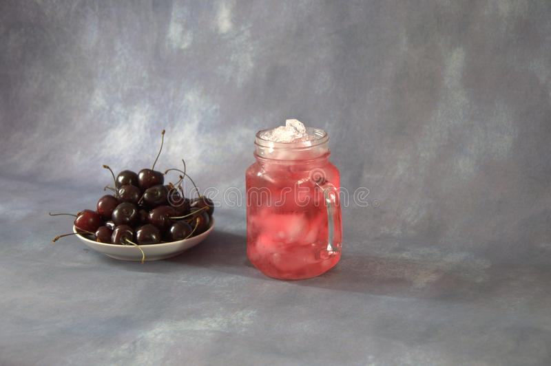 Some fresh cherry fruits on a plate and a mug of cherry juice with ice. Close-up stock photography