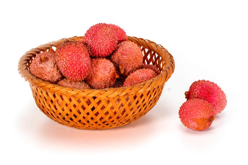 Some fresh litchi fruits or lychee, in wicker bamboo basket isolated on white background, close up stock photography