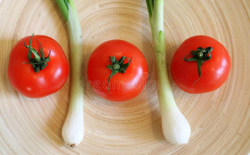 Some fresh tomatoes and spring onion. On marble background royalty free stock images