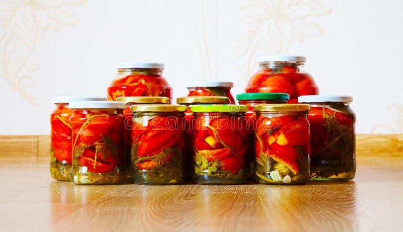 Some glass jars with marinated tomatoes homemade. On the floor royalty free stock photos