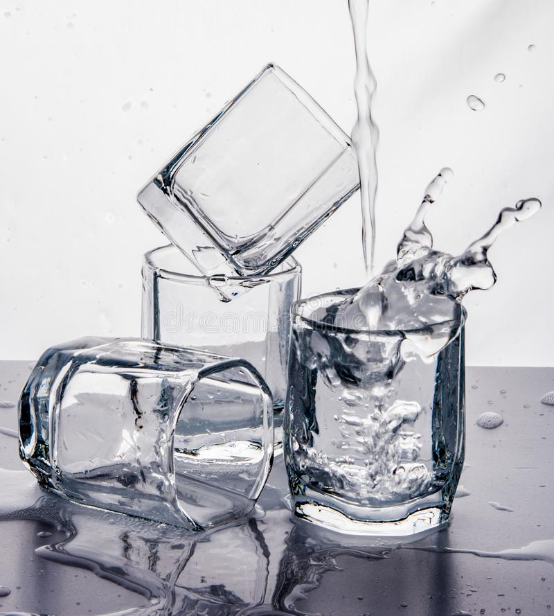 Some glasses water spill black white splash motion mirror. Isolated royalty free stock photography
