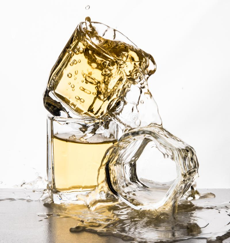 Some glasses water spill black white splash motion mirror. Isolated apple juice whisky stock photo