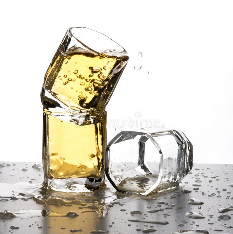 Some glasses water spill splash cold apple juice whisky motion. Isolated royalty free stock photos