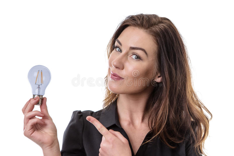 Some great ideas!. Pretty brunette holding onto a lightbulb, looking pleased with her idea stock photo