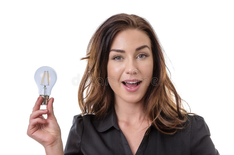 Some great ideas!. Pretty brunette holding onto a lightbulb, looking pleased with her idea royalty free stock photography