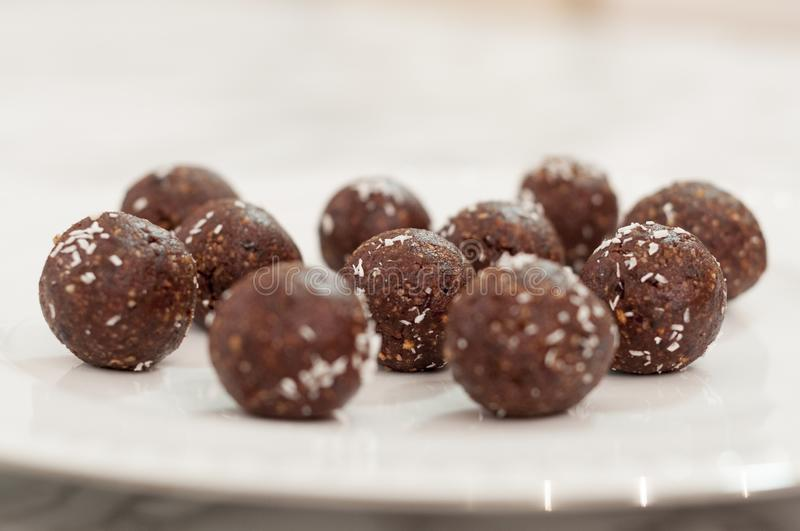 Many handmade chocolate truffles on a white plate royalty free stock images