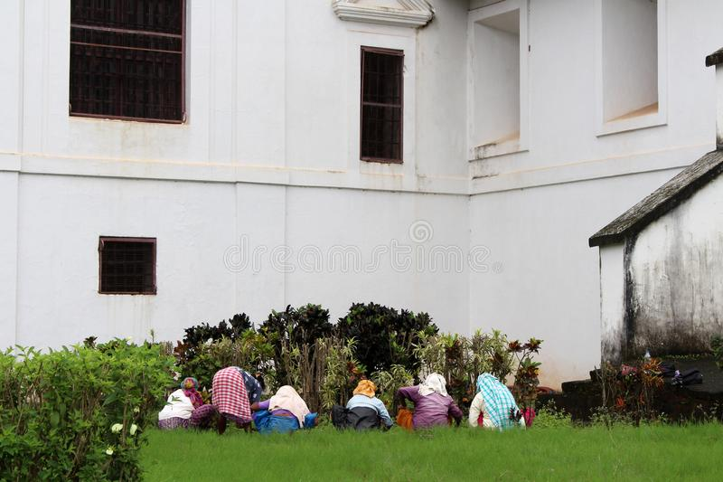 Some Indian ladies are gardening around Se Cathedral of Old Goa stock photography