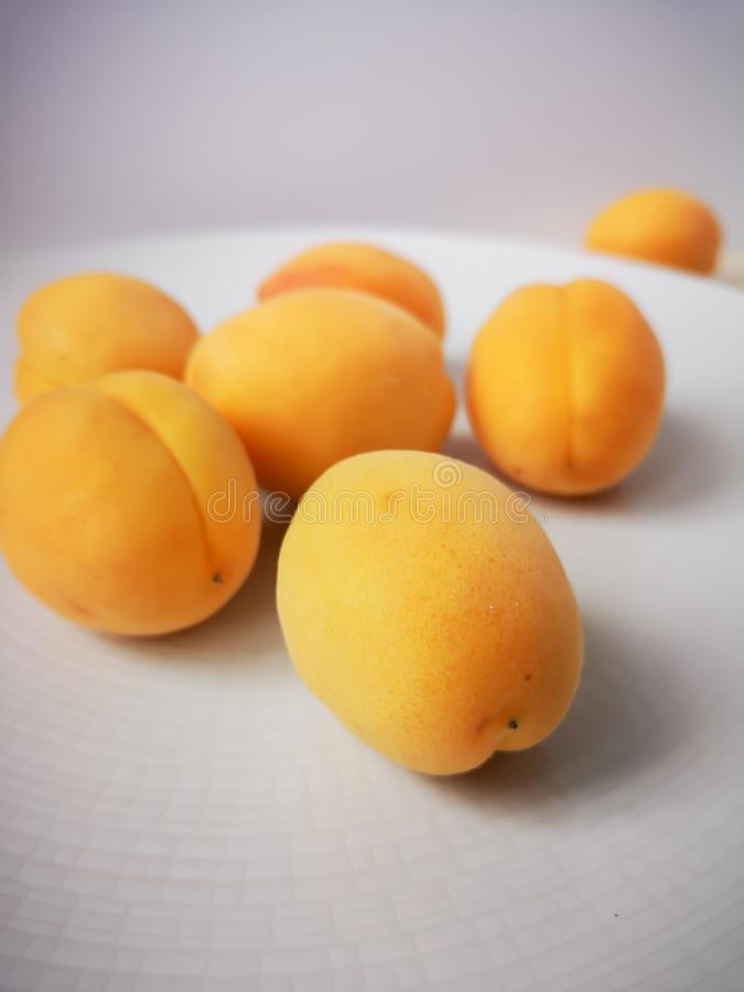 Some juicy ripe sweet apricots lie on a large round white plate that stands on a wooden table. stock images