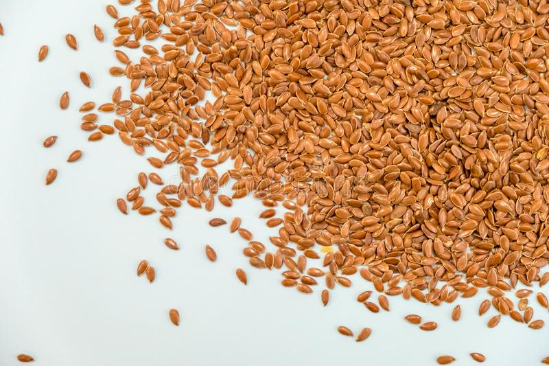 Some linseeds spread out on blue background seen from above. wooden spoon. Close up stock image
