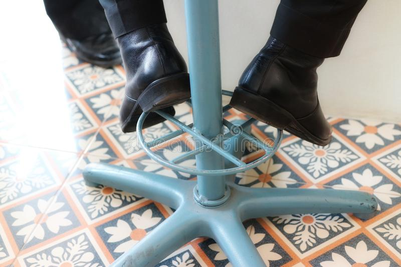 Some of the male businessmen legs are sitting on a vintage iron chair.  Put on black shoes royalty free stock image