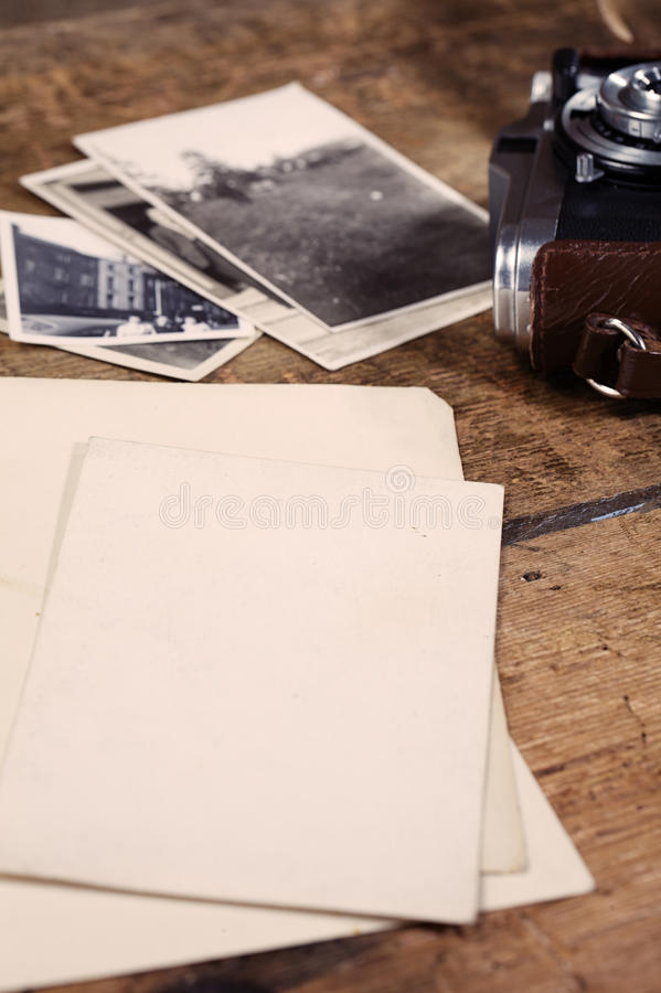 Some old photos and vintage camera on wooden table