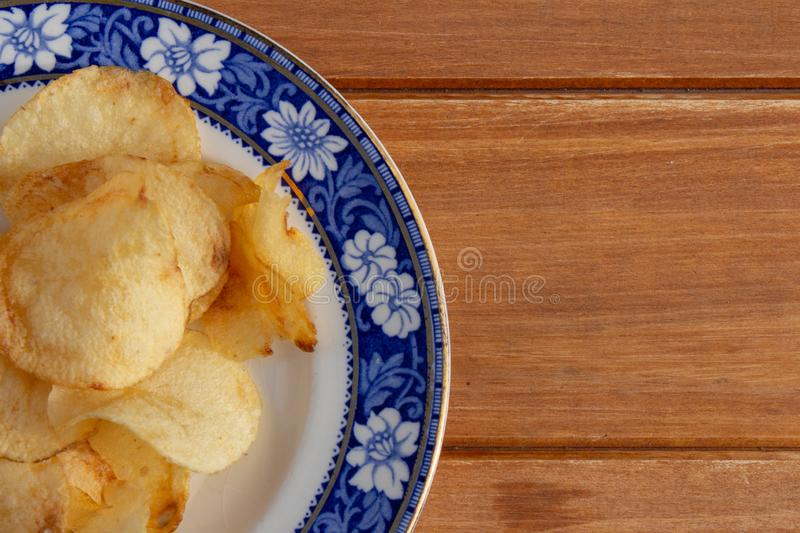 Some papafritas on a plate of bluish and golden colors. Rustic wooden board with food. Scrap or unhealthy food stock images