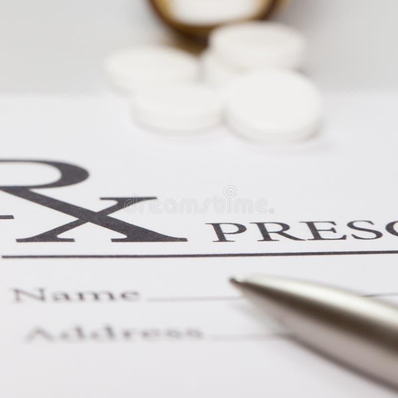 Some pills and a pen over medical prescription form - close up studio shot stock image
