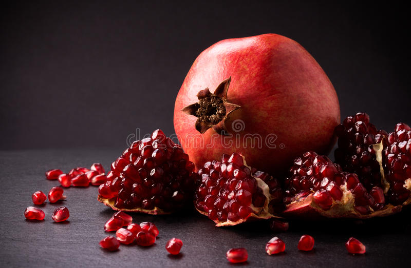 Some red pomegranates on black slate plate. Some red juicy pomegranate, whole and broken, on black slate plate royalty free stock photos